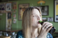 Blonde Woman with Beautiful Blue Eyes Drinks a Bottle of Beer Stock Photography