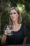 Blonde Woman with Beautiful Blue Eyes and Glass of Water Stock Images