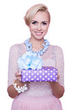 Blonde woman with beautiful smile giving colorful gift box. Christmas. Holiday Stock Photo