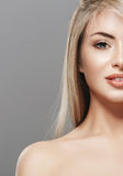 Blonde woman beauty half-face portrait close-up isolated on gray background Stock Photography