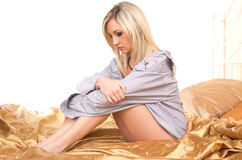 Blonde woman on bed. Studio portrait of young beautifu caucasian blonde woman on bed Royalty Free Stock Photos