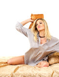 Blonde woman on bed. Studio portrait of young beautiful caucasian blonde woman on bed, throwing a pillow against white background Royalty Free Stock Photography
