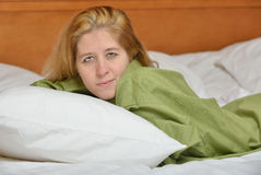 Blonde woman in bed wearing men's shirt Royalty Free Stock Photos