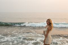 Blonde woman in beige cocktail dress by the sea. Blonde woman in beige cocktail dress against blurred backdrop of sea and waves Royalty Free Stock Photography