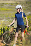 Blonde woman with bike. Wearing helmet in the country Stock Photos