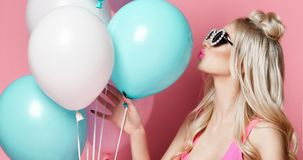 Blonde woman on birthday party having fun with pastel color air balloons blow kiss in round sunglasses stock photos