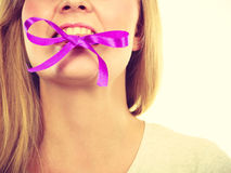 Blonde woman biting decorative purple bow Stock Images
