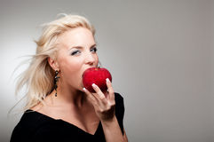 Blonde woman biting red apple Stock Image
