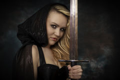 Blonde woman in a black cape with a sword Royalty Free Stock Photography