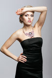 Blonde woman in black dress and necklace Stock Images
