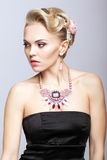 Blonde woman in black dress and necklace Stock Photo