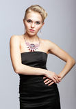 Blonde woman in black dress and necklace Stock Photography