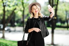 Blonde woman in black hat and leather jacket and bag using the mobile phone. Young woman taking selfie. Blonde woman in black hat and leather jacket and bag Royalty Free Stock Photos