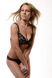 Blonde woman in black latex lingerie on white background Stock Photo