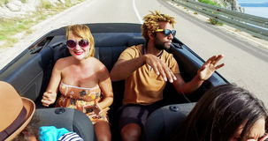 Blonde woman and black man riding in the back of convertible, color graded. Beautiful blonde woman and handsome african american man riding in the back seat of stock video footage