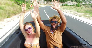 Blonde woman and black man waving arms riding in the back seat of convertible stock footage