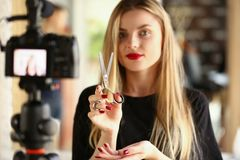 Blonde Woman Blogger Holding Metallic Scissors. Hairdresser Recording Modeling Instrument for Beauty Blog. Hairstylist Showing Cutting Tool on Camera. Girl stock photos