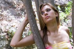 Blonde woman with blue eyes on a tree Royalty Free Stock Photos