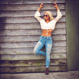 Blonde woman in blue jeans. Blonde woman wearing blue jeans and midriff white top leaning against outside of rustic wooden wall Stock Images