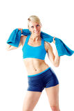 Blonde woman in blue sports wear holding a towel around her shoulder Royalty Free Stock Image