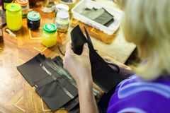 Woman cutting a part of a wallet. Blonde woman in blue unform cutting a part of a wallet with scissors. manufacturing process. jars on the background. close-up Royalty Free Stock Photo