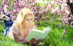 Blonde Woman with Book under Cherry Blossom Royalty Free Stock Photo