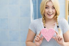 Blonde woman in braids holding heart royalty free stock image