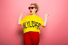 Blonde woman in bright clothes. Attractive woman in yellow T-shirt, red jeans and sunglasses holding her hands back in schock  on pink background with copyspace Stock Photo