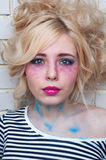 Blonde woman with bright creative make-up near the wall Stock Image