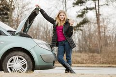 Blonde woman and broken down car on road Stock Photo