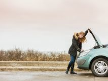 Blonde woman and broken down car on road Royalty Free Stock Photography