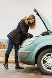 Blonde woman and broken down car on road Stock Photography