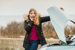 Blonde woman and broken down car on road Stock Images