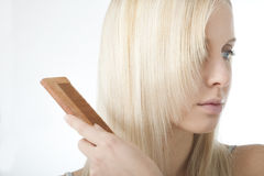 Blonde woman brushing her hair Royalty Free Stock Photography