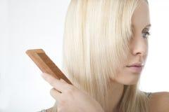 Blonde woman brushing her hair. Beautiful blonde woman brushing her hair royalty free stock photography