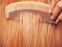 Blonde woman brushing her hair with comb Stock Images