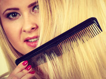 Blonde woman brushing her long hair with comb Stock Image