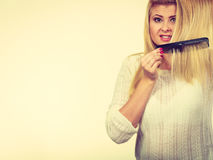 Blonde woman brushing her long hair with comb Royalty Free Stock Images