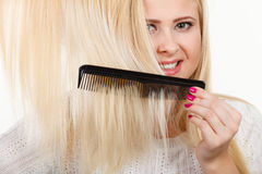 Blonde woman brushing her long hair with comb Stock Images