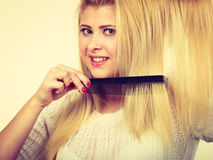 Blonde woman brushing her long hair with comb Stock Photos