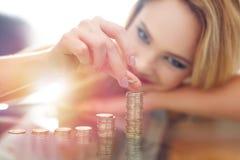 Blonde woman building money column Royalty Free Stock Photos