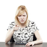 Blonde woman in business attire at desk pointing Royalty Free Stock Photography