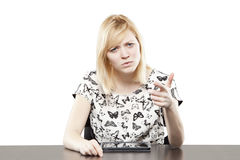 Blonde woman in business attire at desk pointing Stock Photo