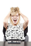 Blonde woman in business attire very angry and upset at desk Royalty Free Stock Images
