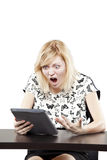 Blonde woman in business attire very angry and upset at desk Royalty Free Stock Photography