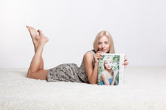 Blonde woman with calendar. Happy blonde young woman on white whole-floor carpet showing herself in annual calendar of photographer Serg Zastavkin royalty free stock images