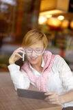 Blonde woman call in restaurant behind glass Royalty Free Stock Images