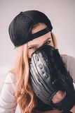 Blonde woman in cap hiding face with baseball glove Stock Photography