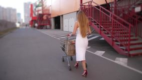 Blonde woman carrying shopping cart to parking lot. Back view of beautiful long haired female in high heels walking with shopping cart from supermarket to stock footage