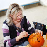 Blonde woman carving pumpkin Royalty Free Stock Image